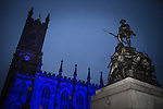 © Joel Goodman - 07973 332324 . 17 November 2013 . Oldham , UK . The church is lit up blue - the war memorial is lit up by on-camera flash.  The Christmas lights are turned on in Oldham Town Centre . Photo credit : Joel Goodman
