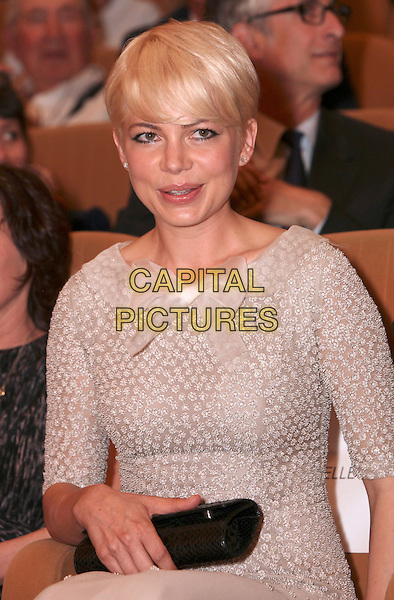 "MICHELLE WILLIAMS.""Meek´s Cutoff"" premiere, 67th Venice International Film Festival, Venice, Italy..September 5th, 2010.half length grey gray dress bow ribbon sleeves beads beaded black clutch bag beige white sitting.CAP/PE.©Peter Eden/Capital Pictures."