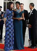 (L-R) Samantha Cameron, First lady Michelle Obama, British Prime Minister David Cameron and U.S. President Barack Obama greet one another on the North Portico of the White House March 14, 2012 in Washington, DC. Cameron is on a three-day visit to the U.S. and he was expected to have talks with Obama on the situations in Afghanistan, Syria and Iran. .Credit: Chip Somodevilla / Pool via CNP