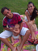 A young local family sitting on a picnic blanket