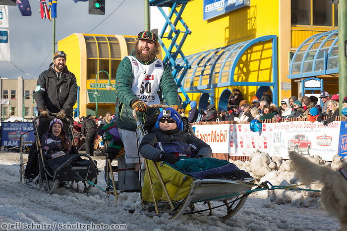 Brian Wilmshurst and team leave the ceremonial start line with an Iditarider at 4th Avenue and D street in downtown Anchorage, Alaska during the 2015 Iditarod race. Photo by Jim Kohl/IditarodPhotos.com