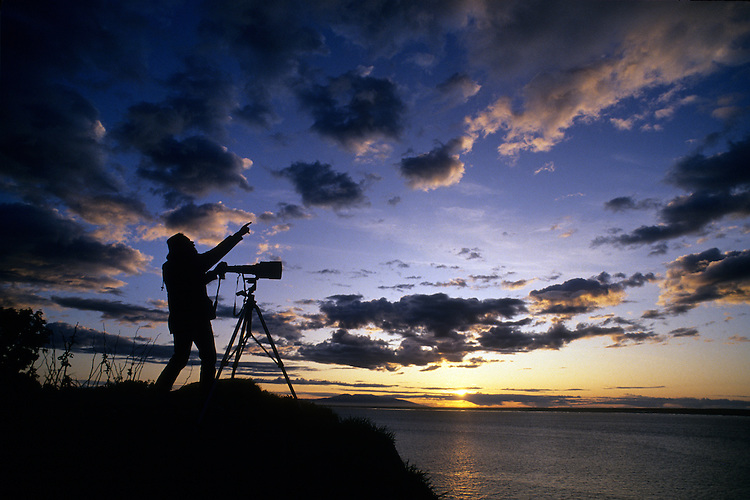 A photographer gestures while making images of the sunset behind Mount Susitna, across Cook Inlet from Anchorage, Alaska.