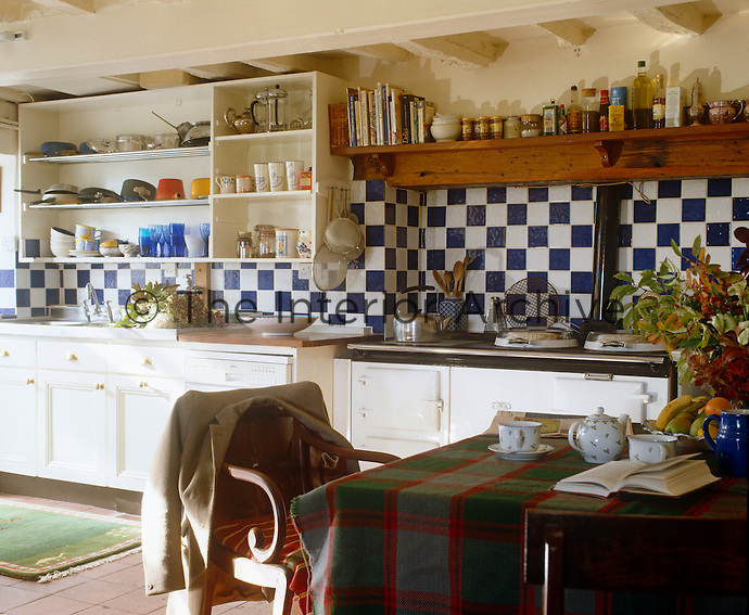 A rough tartan tablecloth and blue and white ceramic tiles create an interesting contrast in this rustic kitchen