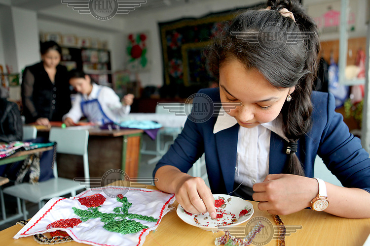 A girl threading beads at a school in Ispisor Jamoat Village where youths aged 15 and 16 learn practical life skills.