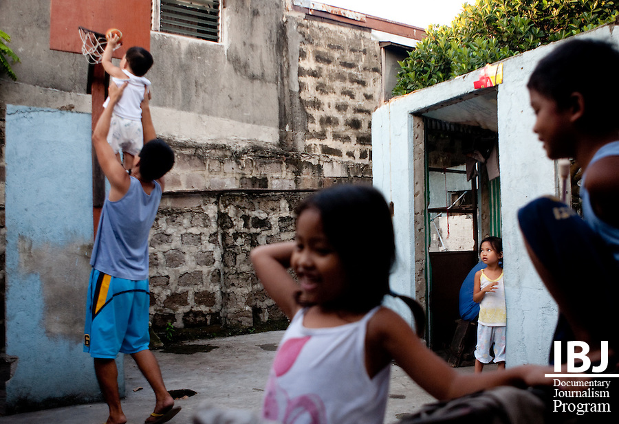 A group of children play in an abandoned house.  The roof has fallen off or been scavenged and only the walls now stand.