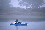 Kayaker in kayak in calm still water of estuary in fog, Morro Bay State Park, California
