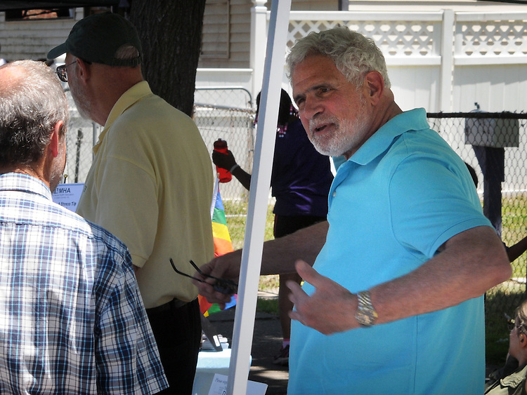 Volunteer at the REHER Center for Immigrant Culture & History Booth is discussion with a visitor at the 11th Annual Mid-town Make a Difference Day Celebration on Franklin Street, in Kingston, NY on Saturday, June  18, 2016. Photo by Jim Peppler. Copyright Jim Peppler 2016.
