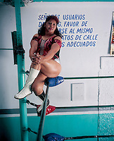 "Tania la Guerillera, one of the more senior of Luchadoras ""women wrestlers"" still in the ring, teaches, is a mother, and has a beauty salon in the Gym called Salon Tania in the Gymnasio Latinoamericano. Mexico DF,  June 2004."