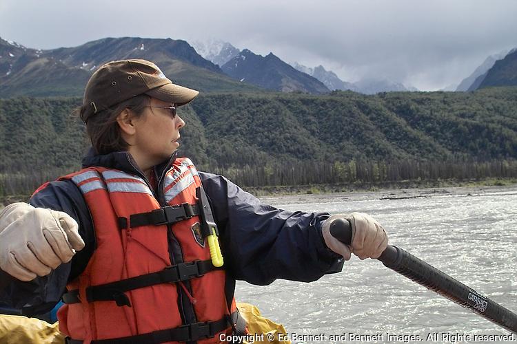 Georgia Bennett rows a raft on the upper Matanuska River as a rain shower approaches.