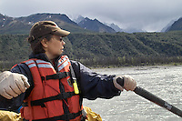 Georgia Bennett rows a raft on the upper Matanuska River as a rain shower approaches.