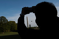 A visitor takes a photo as Marine One, carrying United States President Donald Trump returns to the White House in Washington, D.C. on April 18, 2017. President Trump is returning form a day trip to Kenosha, Wisconsin where he visited Snap-on tools. <br /> CAP/MPI/RS<br /> &copy;RS/MPI/Capital Pictures