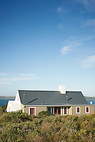 A country style beach house with red painted window frames and corrugated roof.