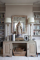 Flanked by two table lamps, an antique icon stands in pride of place on the library desk, against the backdrop of a tarnished mirror