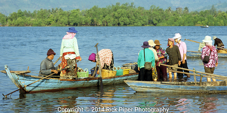 Small crowd of locals buying fresh seafood from small boats on the Sanke river foreshore at dawn, Kampot, Cambodia.