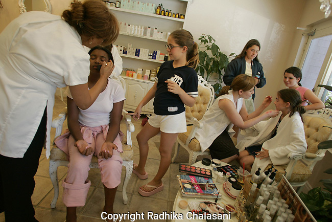 STUDIO CITY, CA-JUNE 10: Makeup artists instruct Sierra Worthy (11) (L) and Emily Andrews (12) (R) in the use of makeup at a spa party as their friends, Caroline Groth (12), Christine Cavanaugh (12) and Rachel Goldinger (12), wait their turn at Belle Visage Day Spa June 10, 2004 in Studio City. The spa hosts parties for 9-18 year-olds which cost between 87-119 USD per person. Cake, lunch and limo services are additional. With teens and pre-teens spending more and more money on health and beauty products a growing number of American spas are providing services to young people.(Photo by Radhika Chalasani)