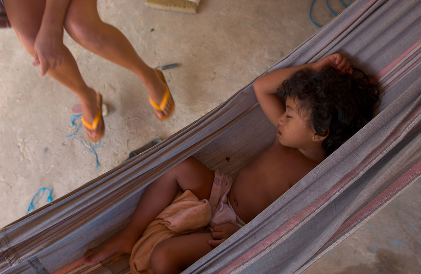 A mother watches her daughter sleepn in a hammock under a shady veranda in Salvaterra, on the island of Marajo (acute accent on the final o) at the mouth of the Amazon. The size of Switzerland, Marajo is a vast expanse of wilderness and cattle and water buffalo ranches, offering a close look at rural life in equatorial Brazil. (Kevin Moloney for the New York Times)
