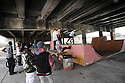 Makeshift skateboard park under interstate..