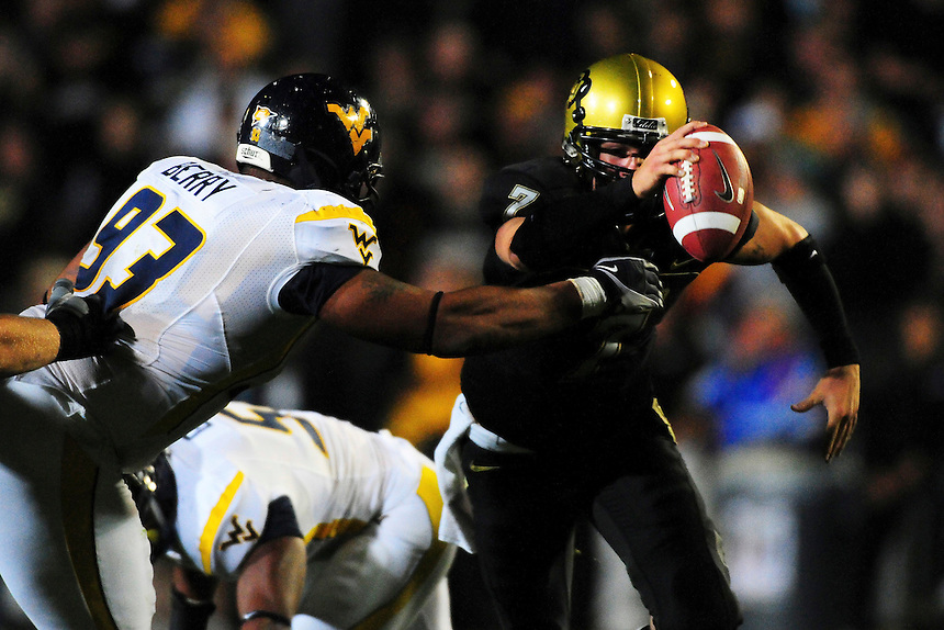 18 September 08: West Virginia defensive lineman Scooter Berry (in white) puts pressure on Colorado quarterback Cody Hawkins. Hawkins was sacked on the play and fumbled the football. The Colorado Buffaloes defeated the West Virginia Mountaineers 17-14 in overtime at Folsom Field in Boulder, Colorado. For Editorial Use Only.
