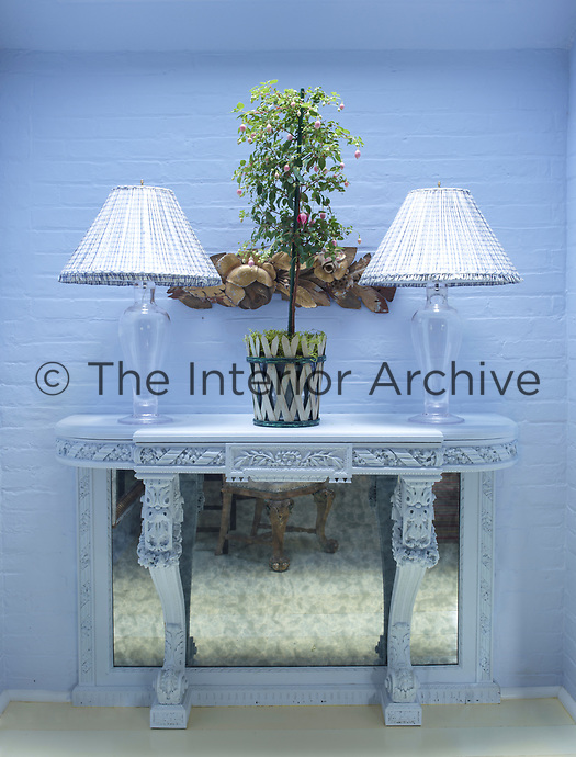 Two glass table lamps with white shades stand on a console table. A silver panel beneath the table reflects light into the room. The brickwork behind is painted blue.