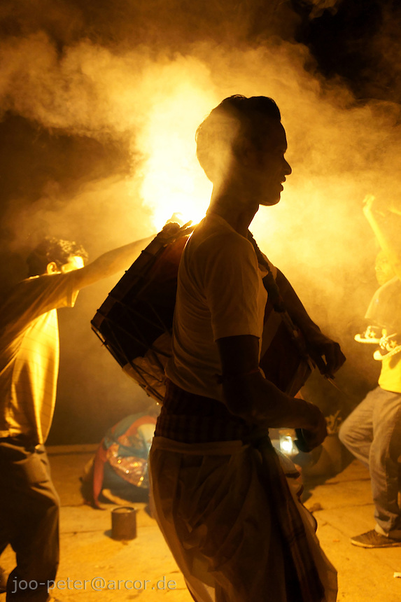 Hindu worshipper chant, dance  and play music for goddess Kali at Ganga river in the night