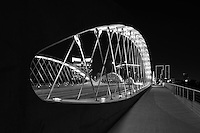 Took this black and white photo of the urban Seventh Street Bridge in Fort Worth  from the pedestrian walkway at night with the city downtown buildings in the background showing the  downtown cityscape.