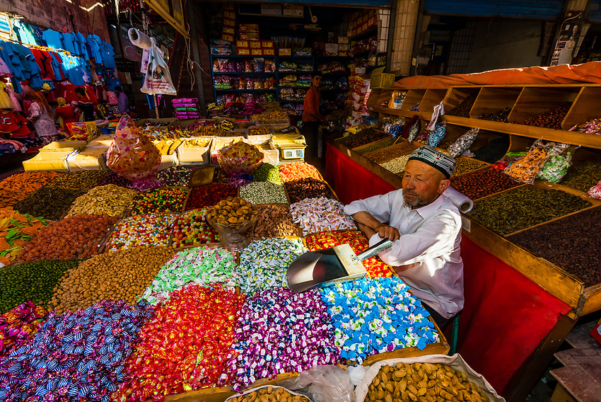 A shopkeeper selling sweets, nuts and dried fruit. Kashgar is an oasis city in Xinjiang Province, China.  It is the westernmost city in China, located near the border with Afghanistan, Kyrgyzstan, Pakistan, and Tajikistan. It was a stop on the Silk Road. Uyghur people are a Central Asian people of Muslim Turkic origin. They are China's largest minority group.