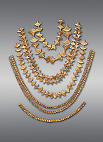 Mycenaean gold necklaces from the Mycenae chamber tombs, Greece. National Archaeological Museum Athens. Grey Background<br /> <br /> From top to bottom: <br /> <br /> Top four  necklaces in the shape of papyrus flowers .<br /> <br /> Fifth necklace down in the shape of Ivy leaves from tomb 91 Cat No 3186<br /> <br /> <br /> Bottom necklace with beads in the shape of hangimng scrolls from tomb 25 Cat No 2478.