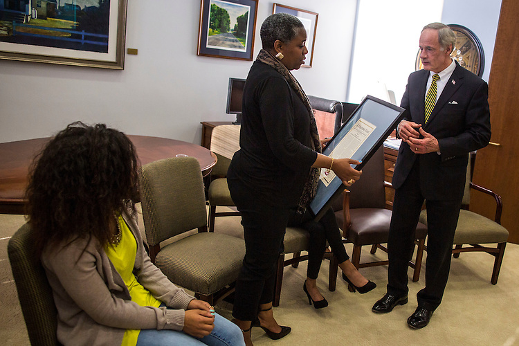 UNITED STATES - APRIL 14 - Sen. Tom Carper, D-Del., presents the Congressional Record signifying the memoriam of the late U.S. Capitol Police Offer Vernon Alston, on behalf of Delaware delegation, to his wife, Nicole Alston, on Capitol Hill, in Washington, Thursday, April 14, 2016. (Photo By Al Drago/CQ Roll Call)