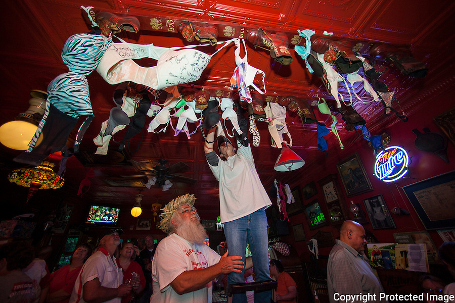 A patron of The Holler House bar in Milwaukee, Wisconsin, participates in the Great Bra Rehanging event on June 14, 2013.  A Milwaukee city inspector ordered Holler House owner Marcy Skowronski to take the bras down in April, saying they were a fire hazard.