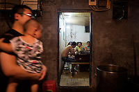 People eat hotpot at one of the indoor rooms at An Pang hotpot in an alley above Tiyu Road in central Yuzhong district, Chongqing, China.