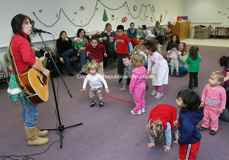 SEYMOUR, CT 12/11/07- 121107BZ01- Lynn Lewis, of Trumbull, plays her guitar and sings while encouraging children to dance during a program at the Seymour Public Library Tuesday. <br /> Jamison C. Bazinet Republican-American