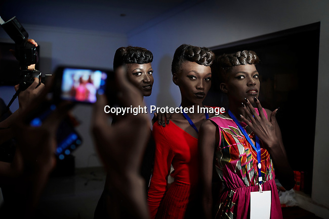 KINSHASA, DRC - JULY 18: Models wait while doing makeup and their hair backstage at Kinshasa Fashion Week on July 18, 2014, at Shark club in Kinshasa, DRC. Local and invited foreign-based designers showed their collections during the second edition of Kinshasa Fashion week. Vanessa Nsul Kilem, age 21, (left) dreams of becoming a super model. She has won local beauty pageants and she was one of 2000 girls casting for the thirty spots to participate in Kinshasa Fashion Week at Shark club in Kinshasa, DRC. (Photo by Per-Anders Pettersson)