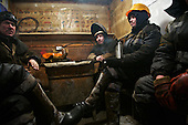 """Men working for the oil and gas prospecting company """"Bashneft"""" sit together in the smoking room. Typically, they work in the cold, isolated Arctic tundra for the entire winter, returning to civilisation only in spring."""