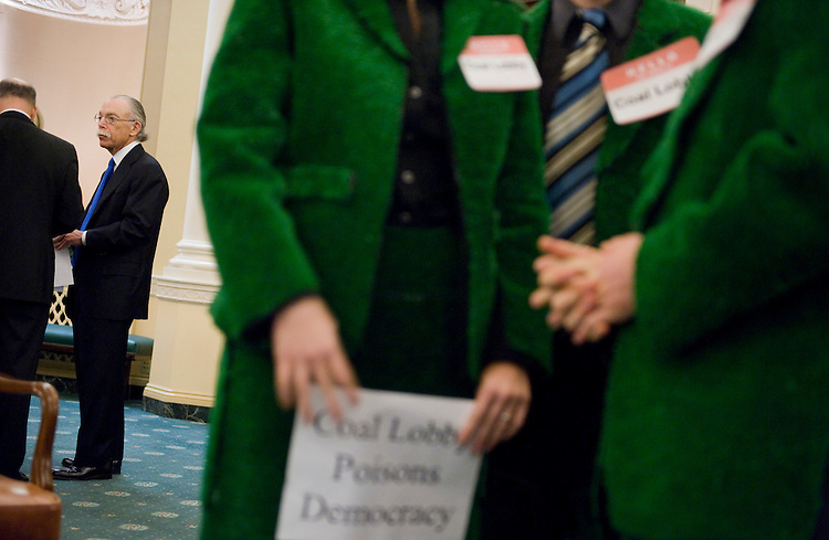 "Jack Bonner, left, president of Bonner & Associates, waits to tesify at a hearing before a Select Committee on Energy Independence and Global Warming entitled ""Fraudulent Letters Opposing Clean Energy Legislation, Oct. 29, 2009.  An employee of Bonner & Associates sent forged letters to Congress opposing climate change legislation.  At right, protesters with the Avaaz Action Factory wear an astroturf suit to protest ""fake grassroots support for the coal industry."""