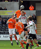 ATTENTION SPORTS PICTURE DESK<br /> Pictured: Alex Baptiste of Blackpool (TOP) heads the ball away from a Swansea corner kick, who battles against Alan Tate of Swansea in front of him.<br /> Re: Coca Cola Championship, Swansea City Football Club v Blackpool at the Liberty Stadium, Swansea, south Wales. Saturday 24 October 2009