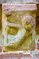 Norman Romanesque exterior corbel no 47  - sculpture of a a bald dancing female dressed in a tight filling tunic. The image is probably a warning against the sexual senses that can be aroused by dancing. The figure has her legs crossed and appears to be recoiling from an impending violation. The Norman Romanesque Church of St Mary and St David, Kilpeck Herefordshire, England. Built around 1140