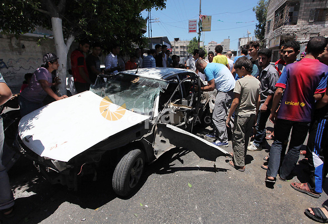 Palestinian men gather behind a car in which at least four people were injured shortly after it was hit by an Israeli airstrike in Gaza, 25 July 2014. More than 820 Palestinians have been killed in Gaza since the start of the Israeli offensive on 08 July. In Israel, so far 32 soldiers and three civilians have died. Photo by Ashraf Amra