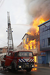 Firemen extinguishing a building fire on the day of the New Year celebration in Paramaribo, Suriname.  Suriname is South America's largest consumer of fireworks/firecrackers and famous for its New Years celebration during which dozens of people are injured each year and buildings often catch fire.
