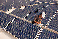 A worker inspects solar panels on the roof of a building