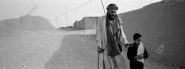 Gul Mohammad, blind, one leg left after mine explosion, is led by his son, Noorahmad, to beg in a mosque in order to support his family. Kandahar, Afghanistan. July, 2003.