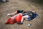 © Joel Goodman - 07973 332324 . 20/07/2013 . Suffolk , UK . Four girls lie asleep on the ground in a huddle . The Latitude music and culture festival in Henham Park , Southwold . Photo credit : Joel Goodman