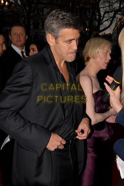 "GEORGE CLOONEY & RENEE ZELLWEGER .Attending the ""Leatherheads"" European Film Premiere held at the Odeon cinema, Leicester Square London, England, 8th April 2008..half length black jacket  funny face strapless purple dress side profile being interviewed .CAP/IA.©Ian Allis/Capital Pictures"