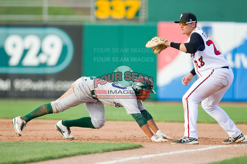 Christopher Bostick (20) of the Beloit Snappers dives back to first base as Balbino Fuenmayor (28) of the Lansing Lugnuts waits for a pick-off throw at Cooley Law School Stadium on May 5, 2013 in Lansing, Michigan.  The Lugnuts defeated the Snappers 5-4.  (Brian Westerholt/Four Seam Images)