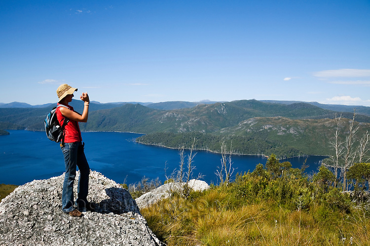 A hiker looks out over Lake Mackintosh from Mount Farrell.  Tullah, Tasmania, AUSTRALIA