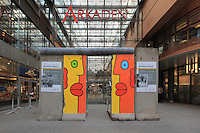 Entrance to the Potsdamer Platz Arkaden building, a huge shopping centre and car park, and a section of Berlin Wall painted by Thierry Noir, celebrating 25 years since the fall of the Wall (in 2014), in the Potsdamer Platz quarter, Tiergarten, Berlin, Germany. Picture by Manuel Cohen