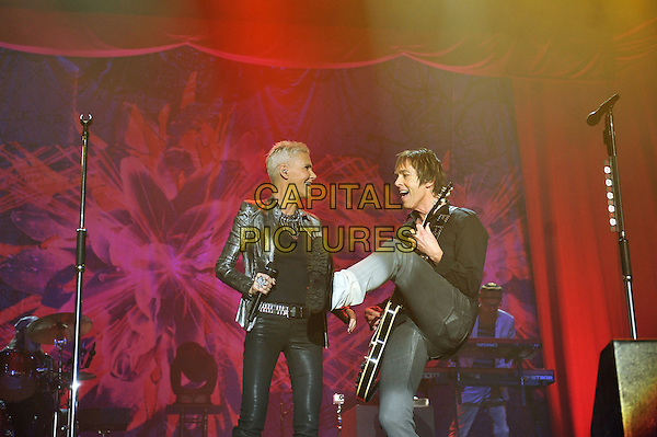 Marie Fredrikson and Per Gessle.Roxette performing live in concert at Wembley Arena, London, England. .15th November 2011.on stage gig performance music half length black top silver blazer full guitar leg up foot kick kicking side profile  .CAP/MAR.© Martin Harris/Capital Pictures.