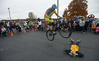NWA Democrat-Gazette/ANDY SHUPE<br /> Jeff Lenosky, a professional freeride and trials mountain bicycle rider from Sparta Township, N.J., bunny hops Saturday, Nov. 11, 2017, over Casimir Lipinski, 10, of Fayetteville during a celebration for Lewis and Clark Outfitters' newly expanded bike shop at the company's store in Fayetteville. Lenosky gave two shows, leaping over obstacles and even jumping into the bed of a full-size pickup truck.