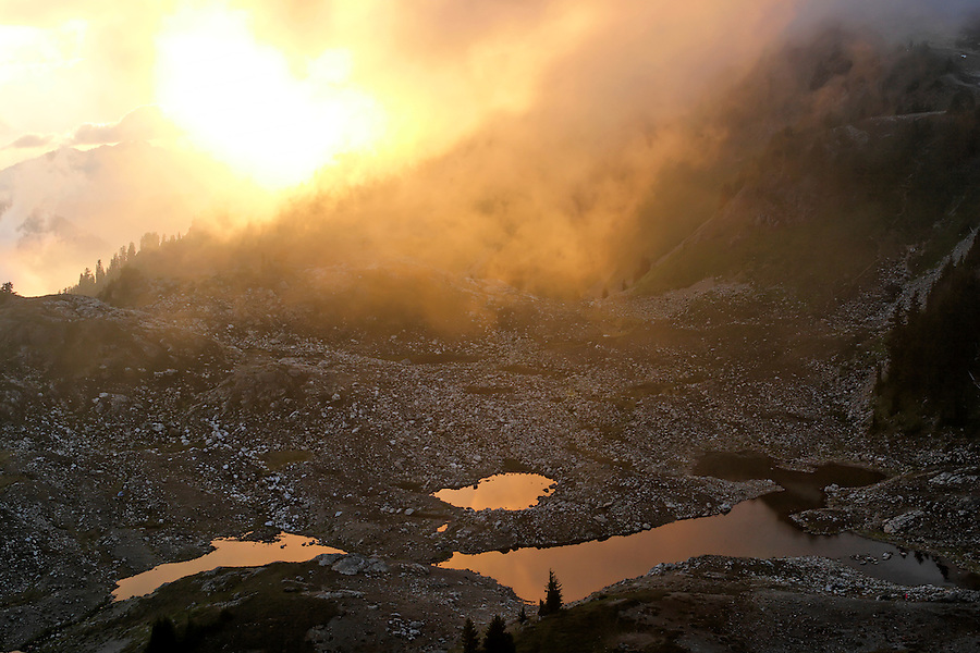 View of sun setting over subalpine lakes below Yellow Aster Butte, North Cascades, Whatcom County, Washington, USA