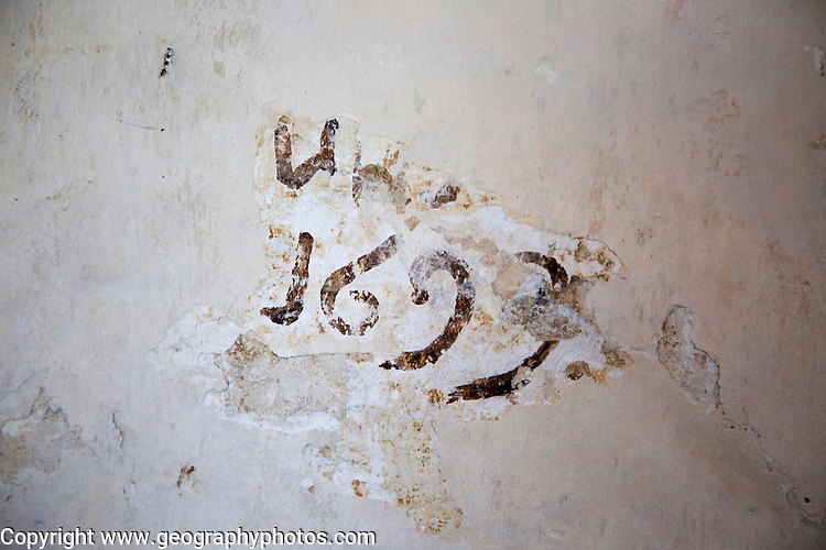The date 1699 emerging from multiple layers of wall painting, building interior medieval church feature, Inglesham, Wiltshire, England,
