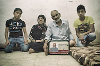 81 years old man with his wife and two grand sons. He adopted them after his son died in the war with Israel in 2006. He is showing the picture of him younger and the village he comes from in Palestine called Tabeliade . The picture of him remind of the prison registration picture as a prisoner of hope. Shatila, Beirut, Lebanon August 2015